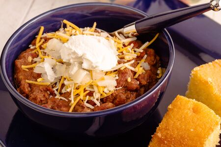 cornbread: Close up of meat chili with red kidney beans, shredded cheese and sour cream in blue bowl with cornbread Stock Photo