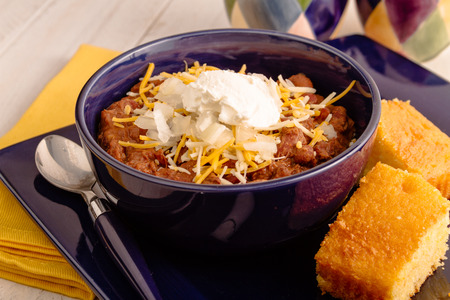 cornbread: Blue bowl of elk meat chili in with sour cream, diced onions, shredded cheese on plate with cornbread