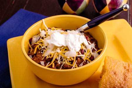 cornbread: Bowl of elk meat chili with toppings and cornbread on yellow plate with blue spoon