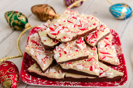 Homemade chocolate peppermint bark sitting on red snowflake plate