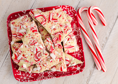 Festive snowflake plate filled with chocolate peppermint bark and 2 candy canes photo