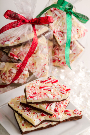 Holiday gifts of chocolate peppermint bark tied with red and green ribbon photo
