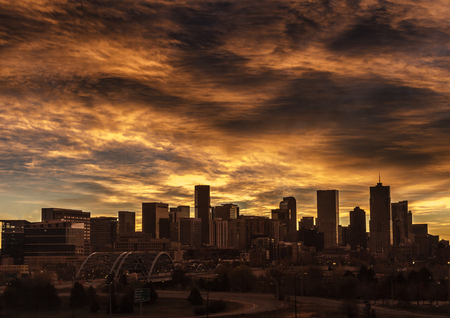 denver skyline with mountains: Dramatic sunrise sky over the city of Denver Colorado