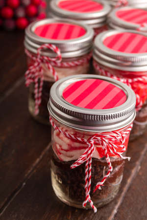 Chocolate peppermint cupcakes in a jar with red and white bakers twine on old brown table photo