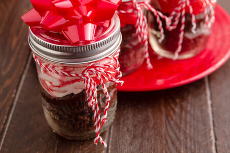 Chocolate peppermint cupcakes in a jar with red and white bakers twine and red bow photo