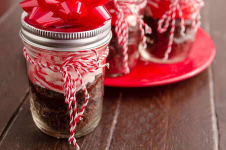 Chocolate peppermint cupcakes in a jar with red and white bakers twine and red bows photo