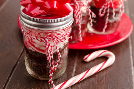 Chocolate peppermint cupcakes in a jar with red and white bakers twine, red bow and candy cane photo
