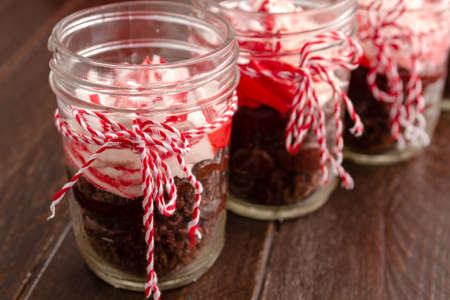 Chocolate peppermint cupcakes in a jar with red and white bakers twine sitting on old brown table photo
