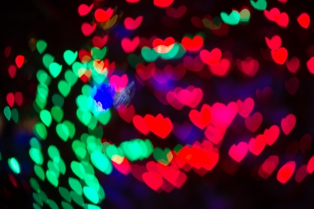 Abstract heart shaped bokeh background of multi colored Christmas lights photo