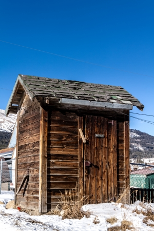 outhouse: Old western style mountain outhouse style bathroom with Office sign on door