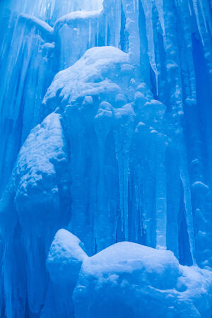 Abstract ice and icicles formations hanging on cold winter day covered in freshly fallen snow Stock Photo