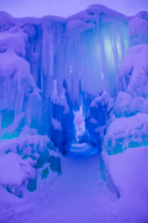 Abstract ice and icicles formations forming ice caves on cold winter day covered in snow and colored lights