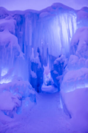 Abstract ice and icicles formations forming ice caves on cold winter day covered in snow and colored lights photo