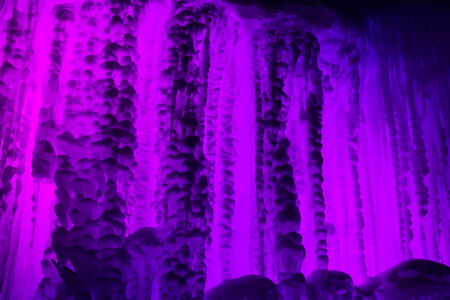 Abstract ice and icicles formations on cold winter night covered in snow and purple colored lights
