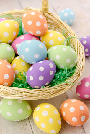 Easter basket with green grass filled with brightly colored polka dot Easter eggs photo