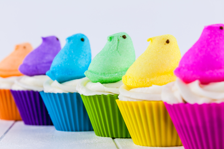 Brightly colored Peeps marshmallow Easter cupcakes arranged in rainbow Stock Photo