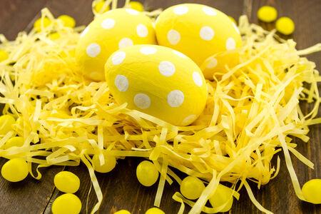 polka dotted: Polka pintada a mano amarillo salpicado de huevos de Pascua en amarillo cesta de Pascua con caramelos de goma Foto de archivo