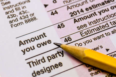 Close up of words Amount you owe on tax form with pencil pointing at words Stock Photo