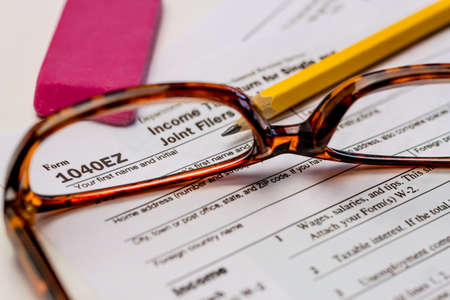 Viewing tax form 1040EZ through glasses with pencil and pink eraser photo
