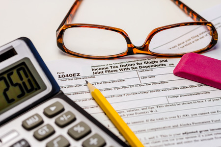 Tax form 1040EZ with calculator, pencil, glasses and pink eraser photo