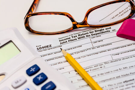 tax form: Tax form 1040EZ with calculator, pencil, glasses and pink eraser