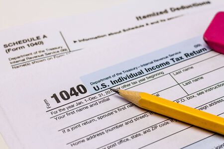 Close Up Of Tax Form 1040 With Schedule A Pencil And Pink Eraser
