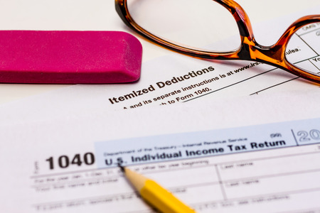 Close up of tax form for itemized deductions with glasses, pencil and pink eraser photo