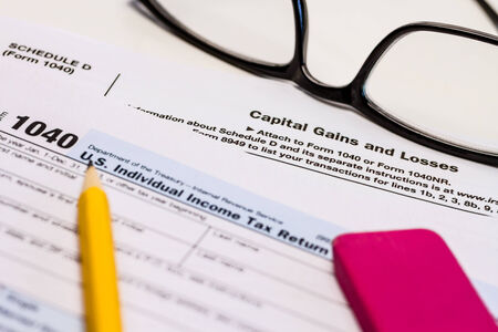 capital gains: Close up of tax form Schedule D for capital gains and losses with glasses, pencil and pink eraser