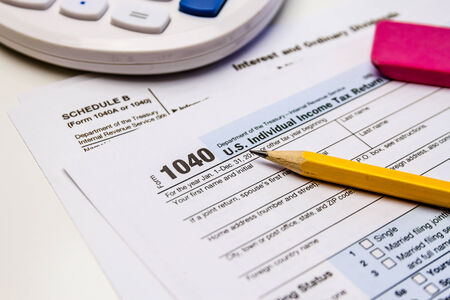 dividends: Close up of tax form Schedule B for interest and ordinary dividends with calculator, pencil and pink eraser