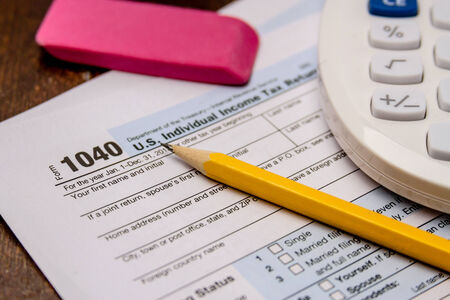Close up of tax form 1040 with pencil, pink eraser and calculator photo