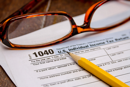 income tax: Close up of tax form 1040 with pencil, pink eraser and pair of glasses