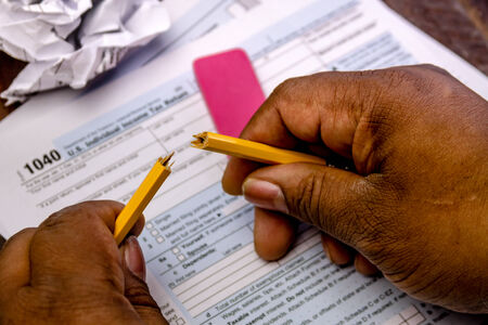 trashed: African american male hands holding broken pencil with tax form 1040 and trashed tax forms Stock Photo