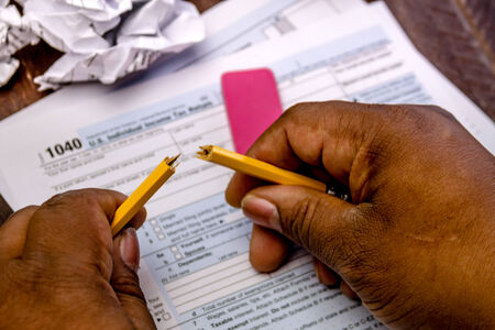 African american male hands holding broken pencil with tax form 1040 and crumpled up tax forms photo