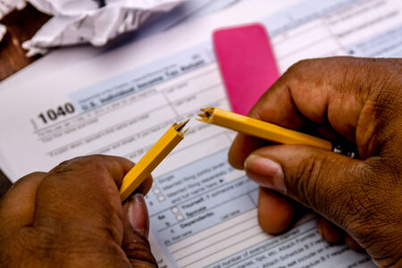 trashed: African american male hands holding broken pencil in frustration with tax form 1040 and trashed tax forms Stock Photo
