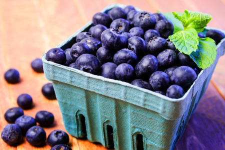 Blue carton full of fresh organic blueberries garnished with mint leaves on wooden table