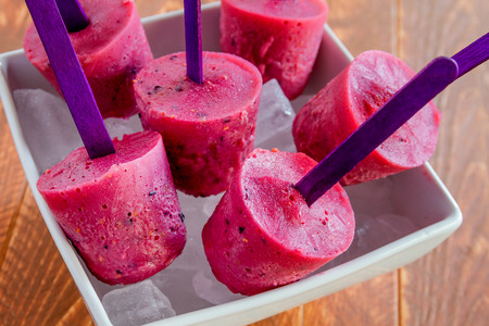 Homemade popsicles made with fresh blueberries, raspberries and yogurt sitting in a white bowl