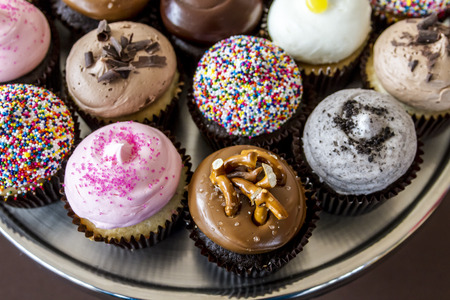 Assorted flavors of decorated cupcakes sitting on silver platter