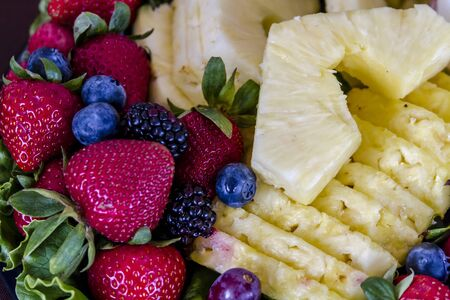 Assorted fruit tray with strawberries, blueberries, grapes, pineapple, blackberries and cheese dip sitting on table photo