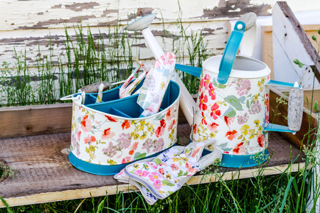Brightly colored gardening tools and gloves with watering can sitting on wooden bench in tall grass photo