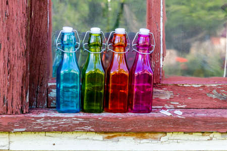 chipping: Colored vintage bottles sitting on old wooden window sill with chipping paint