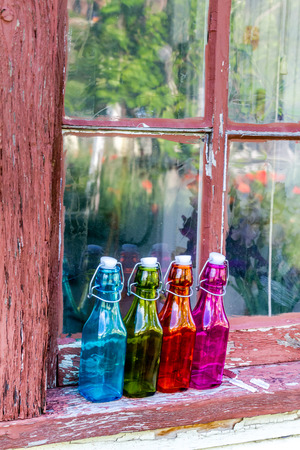 chipping: Colored vintage bottles sitting on old wooden window sill with chipping paint in front of window