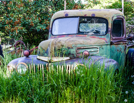Abandoned green and blue pickup truck rusting in a field on summer day photo