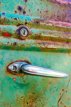Close up of door handle and lock on colorful rusting door of abandoned green pick up truck in field