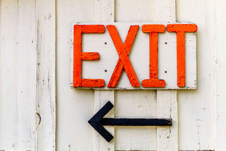 exit sign: Homemade wooden Exit sign with black arrow on side of building