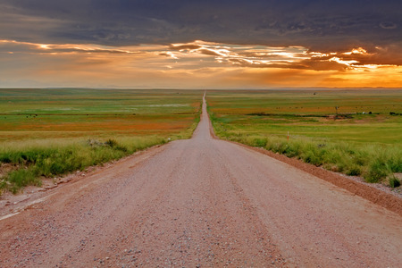Endless dirt road heading off into the distance leading to dramatic sunset sky