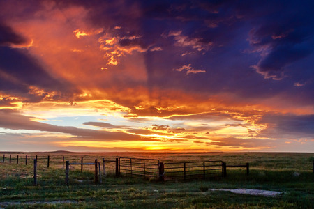 Dramatic sunset clouds with crepuscular rays over prairie ranch field with silhouetted fence line
