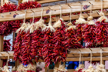Bunches of dried red chili pods hanging as decorative ristras at local farmers market photo