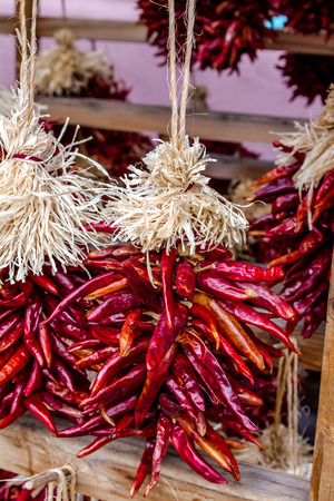 Close up of small bunches of dried red chili pods hanging as decorative ristras at local farmers market photo
