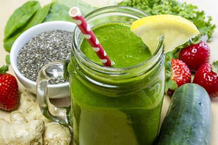 Healthy green juice smoothie surrounded by whole fruits, vegetables and chia seeds with lemon garnish and red polka dot straw Standard-Bild
