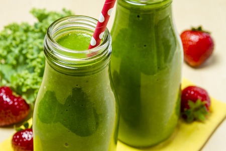 fruit smoothie: Close up of healthy green juice smoothie in glass bottle sitting on yellow napkin with fresh strawberries and kale